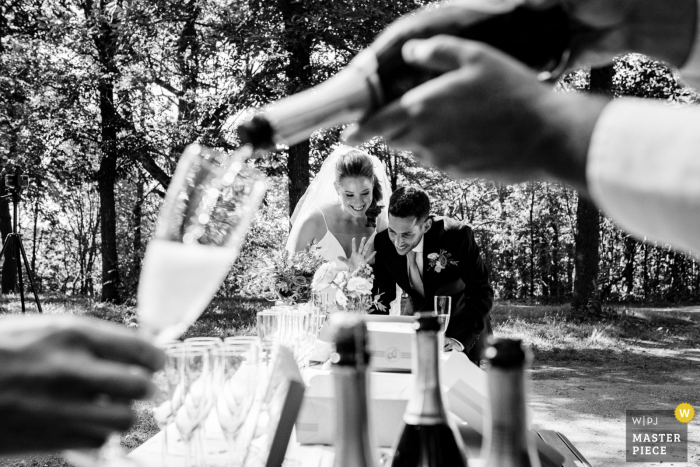 Quebec Canada wedding photo at Parc Mont Royal, Montreal of a Wedding couple chatting with zoom guests on laptop while a server pours prosecco into a guest's glass
