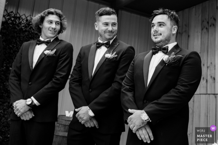 Victoria Australia wedding image of  two groomsmen checking out the groom reaction as the bride enters the room
