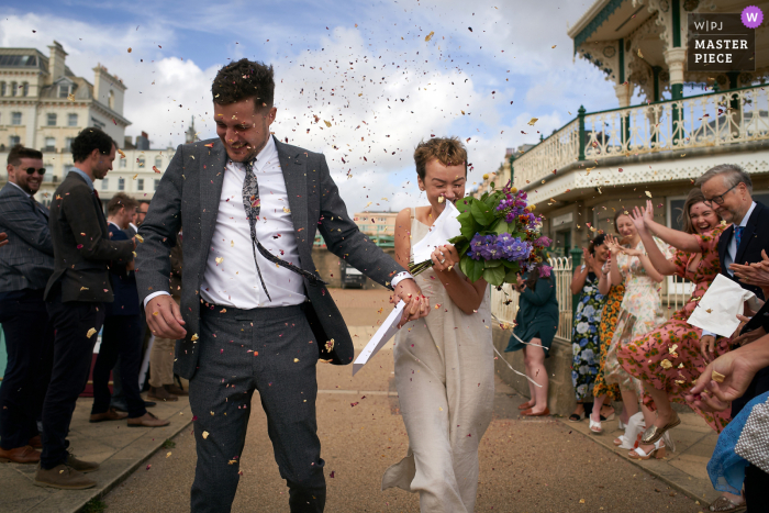 Brighton Bandstand, Brighton Wedding Photographer | the newlyweds run through a spray of confetti