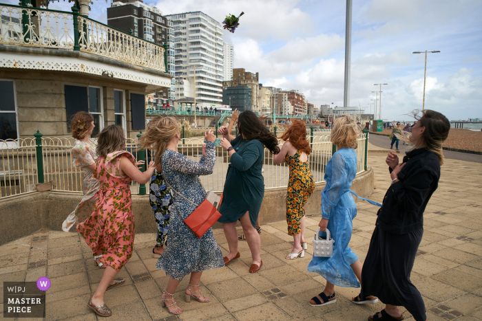 Brighton Bandstand, Brighton | Bride throws her bouquet above and beyong the waiting friends