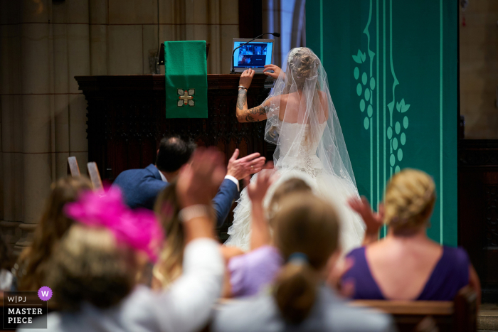 UK wedding photo from a Chiswick, London ceremony during a pandemic - bride getting the laptop link to work mid-ceremony