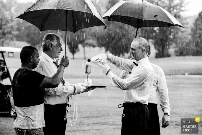 Bulgaria wedding photo from St. Sofia Golf Club as the waiter pours champagne into the glasses of the newlyweds during the ceremony, which took place in heavy rain