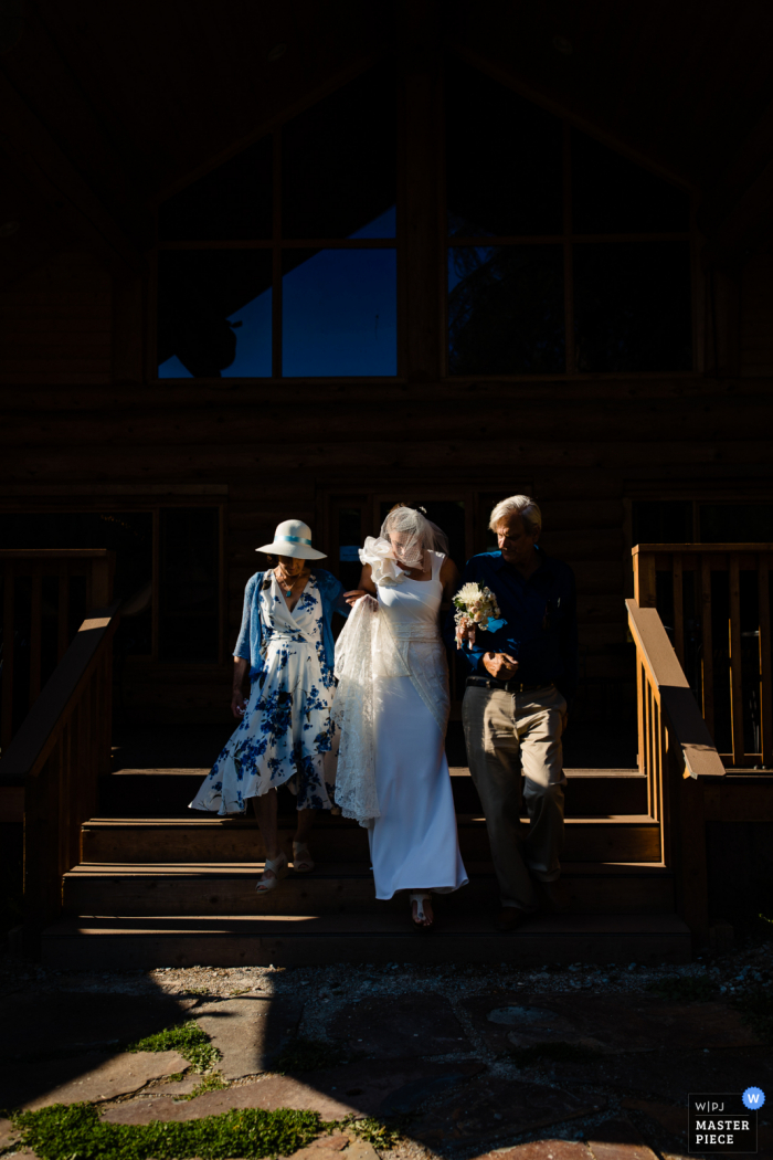 wedding photography from Lochsa Lodge, Idaho showing the bride walking down aisle with mother and father