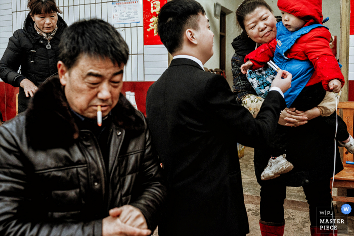 China wedding photography from Chengdu 	Sichuan at The bride's home of The bridegroom joking with a child, He is taking a cigarette for the child
