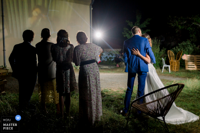 France wedding photography from Vendée with a Night shot of the wedding couple kissing while a slideshow is playing on an outside wall of the venue