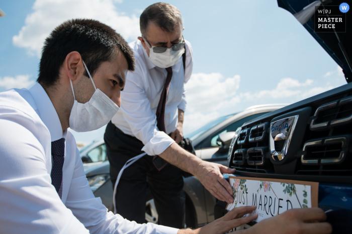 "Izer Hotel, Luleburgaz, Turkey Wedding Image | Groom and father putting ""just married"" sticker on the car"