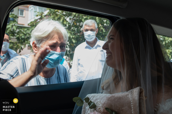 Luleburgaz Wedding Photography   Bride cries in car as the old relative wearing a covid-19 mask waves her goodbye outside the window