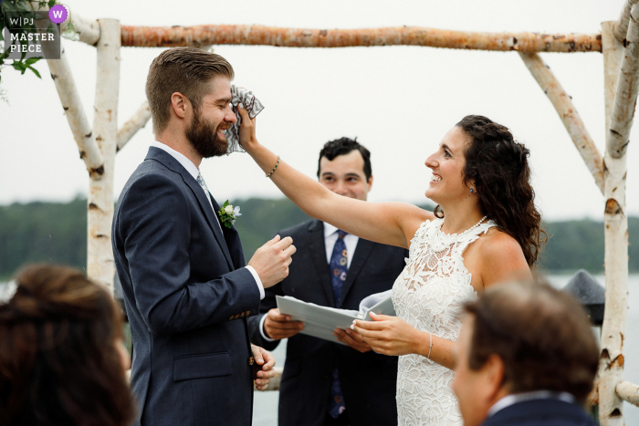 Beach wedding photography from Martha's Vineyard MA at a private house as the Brides wipes the groom's head from rain drops during the ceremony