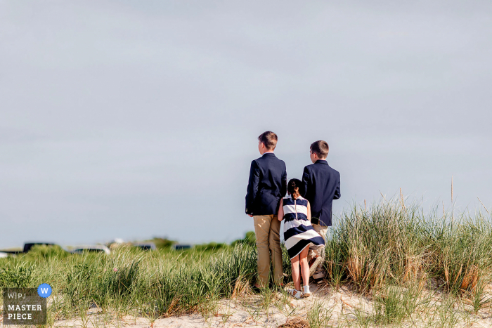 Massachusetts beach wedding photo from Osterville Dowses Beach of Kids waiting for the bride to come during the ceremony