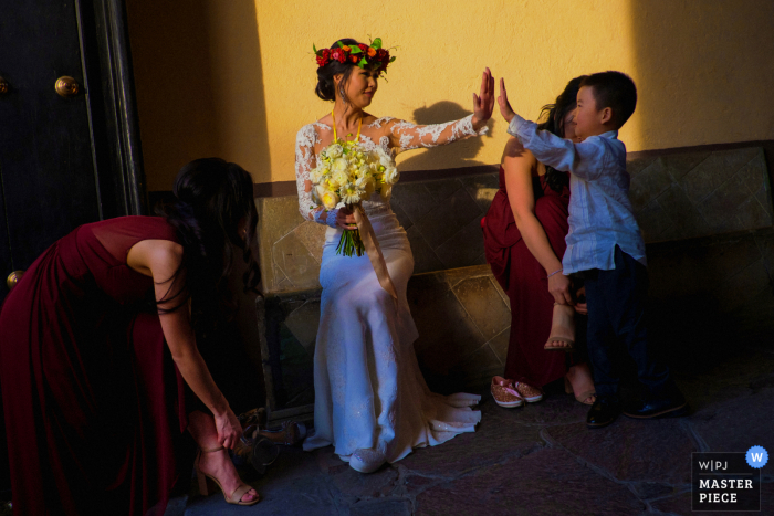 Afternoon sunlit wedding photo from the Instituto Allende, San Miguel de Allende, Mexico showing bride high-fives with her ring-bearer/godson after the wedding ceremony