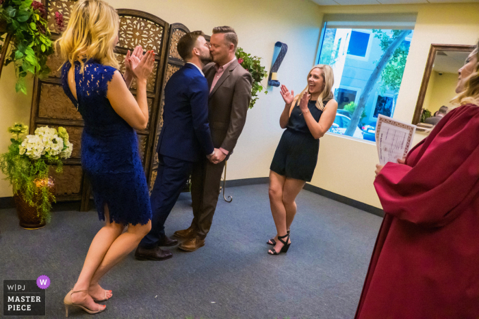 CA wedding photo from Palm Desert - Riverside County Assessor, Palm Desert, California of Two newly-married men kiss as their friends cheer at the county office