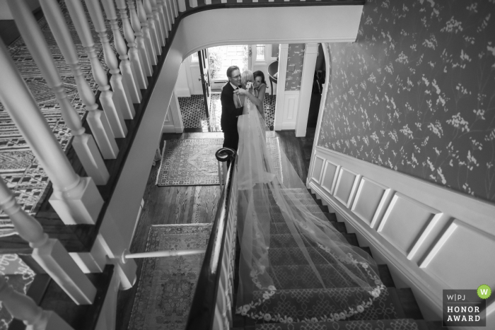 Wedding photography from the Bride's parent's home's in Bloomfield Hills, Michigan of the Bride and parents embracing prior to her leaving the house