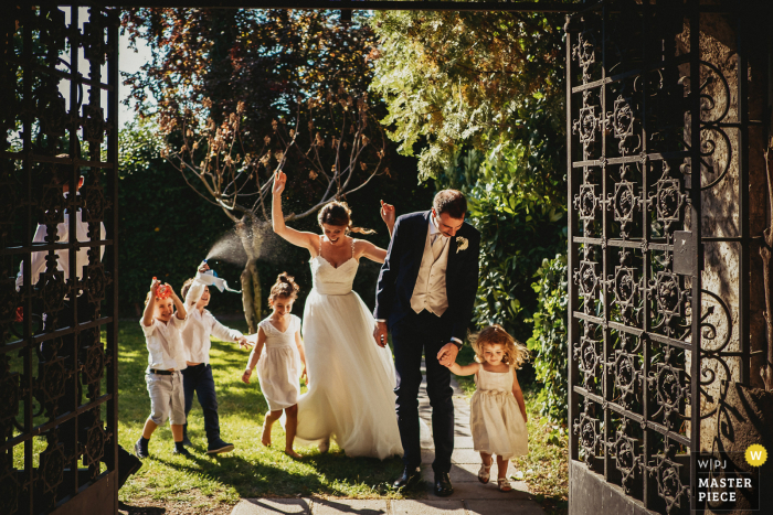 Outdoor reception wedding photo from the venue of Il Conventino di Mentana, Roma showing the Bride and Groom approaching to cake cutting with children following them