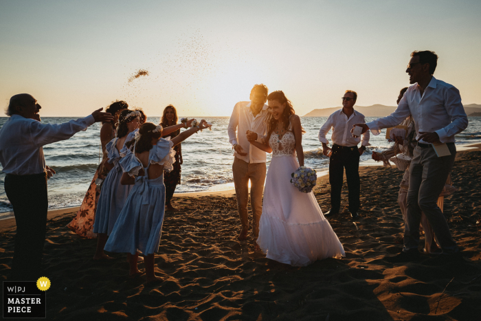 Sunset ceremony wedding photo At the beach near Capalbio, Tuscany of Rice throwing after very intimate celebration on the beach