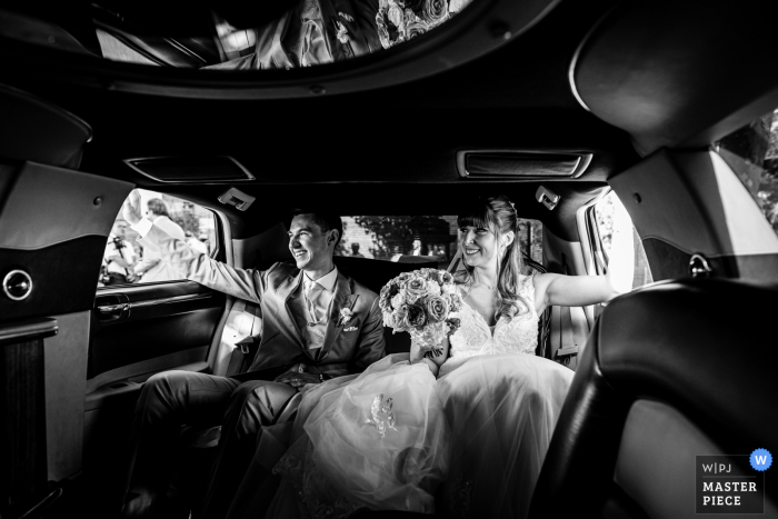 Bridal car wedding photo from Mairie de Merville, France of the Happy couple in the limousine