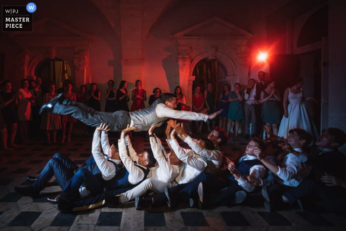wedding photo from Château de Brissac, France showing The groom is jumping during the party