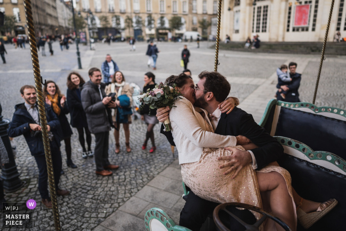 wedding photography from Rennes, France of a Bride and groom on a carousel in front of the guests