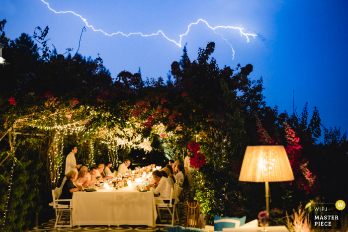 Outdoor wedding photo of lightning at Villa Maçakızı Bodrum/Turkey showing Wedding guests in dinner on a rainy day