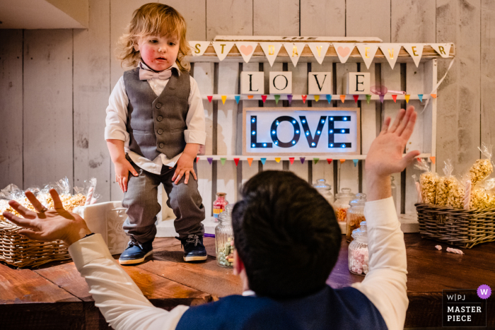 IE wedding reportage photography from the Segrave Barns, Louth, Ireland of a Dad trying to coax toddler page-boy down from on top of the candy-cart