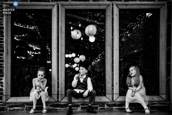 Dublin wedding reportage photographer created this Segraves Barns image of 3 kids in 3 windows at the reception venue