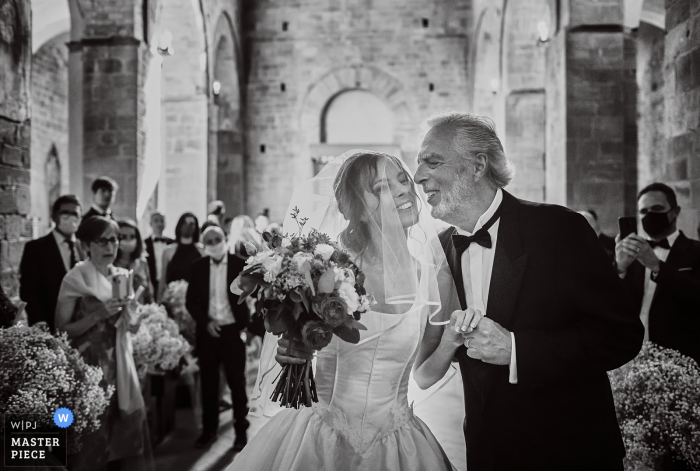 IT wedding photography at the Church of Certaldo - Tuscany of the bride enters and is about to be kissed