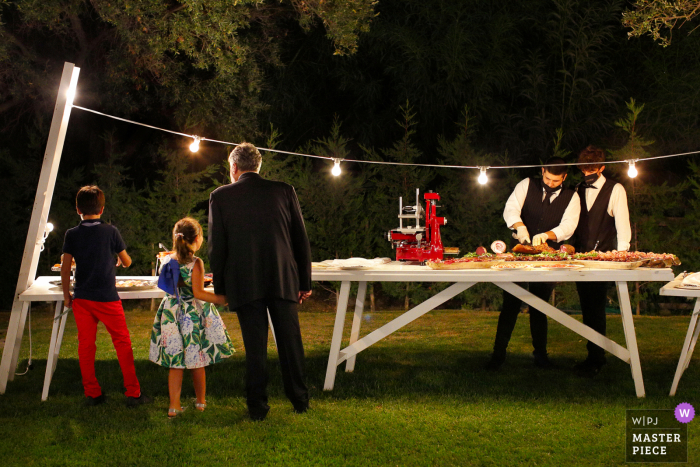 Outdoor reception venue wedding photo from Ristorante La Cascina, Roccella Jonica at the Dinner / reception of Wedding guests observing waiters and Calabrian specialties from the appetizer buffet