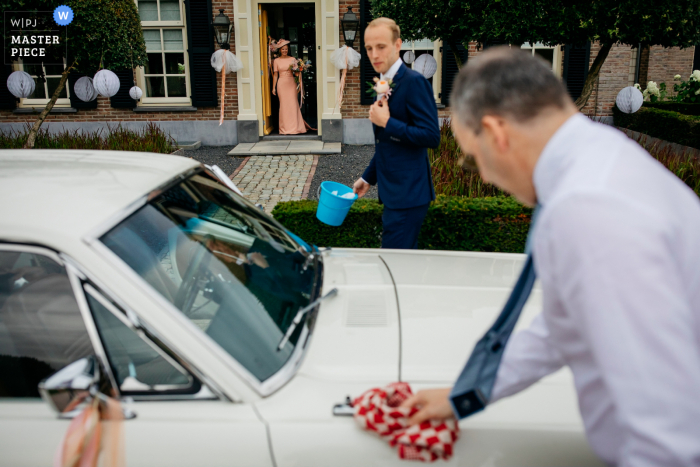 wedding photograph from a home in Rhenen, Netherlands of the bride waiting while her father and her groom are cleaning the car