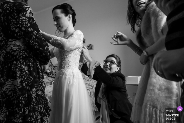 Mantova, Italy Wedding Photo | While the bride is assisting her sister, the friend who fastens the dress looks in vain for help to solve a sudden problem of closing the dress