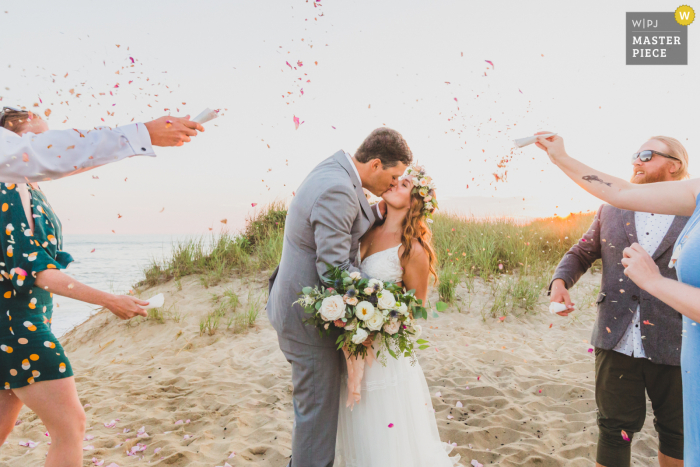 Outdoor, beach wedding photograph from Clark's Cove, Nantucket Island MA of Guests showering the newlyweds in dried flower confetti made by the bride from roses from their favorite beach
