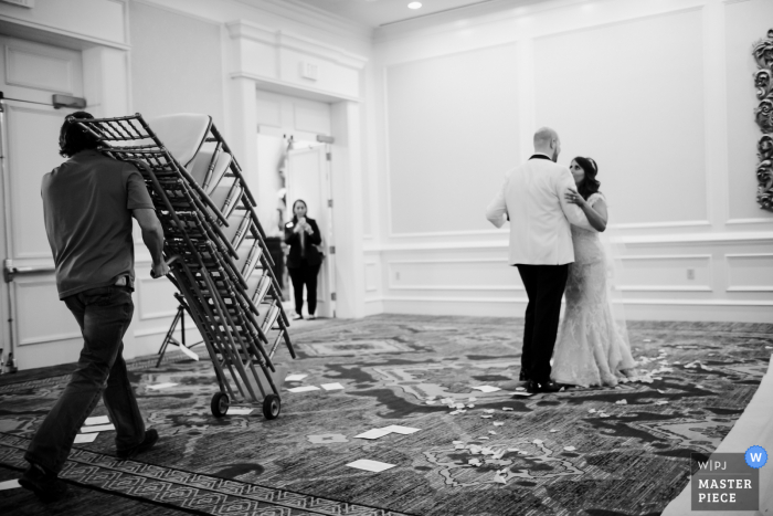 Texas wedding photo from The Westin Riverwalk, San Antonio of the Couple practicing the first dance as chairs are removed from a hotel ballroom
