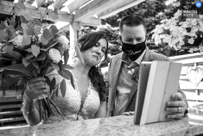 wedding photo from a Backyard ceremony in Ayr, Ontario, Canada from after the ceremony, the bride and groom met with all the guests who couldn't make the wedding due to COVID-19 on a streaming service on their iPAD