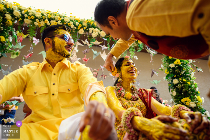 Indian wedding photo from a Mumbai, India of the Haldi ceremony - it brings out some of the best reactions, Capturing the action and reaction together is the key