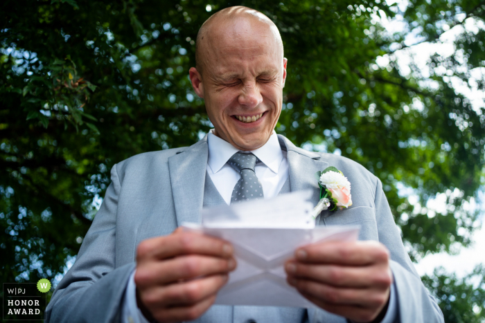 Atlanta Georgia outdoor wedding image of a groom reading a letter from the bride