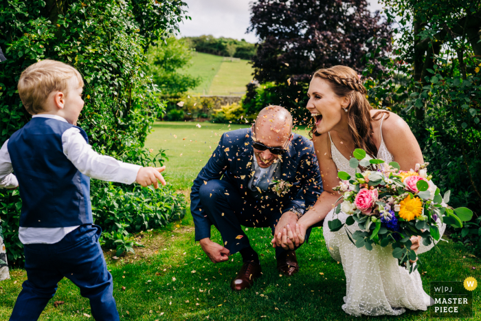 wedding photography from England during the Reception at Pangdean Barn of the Bride and groom crouch down laughing as page boy throws confetti