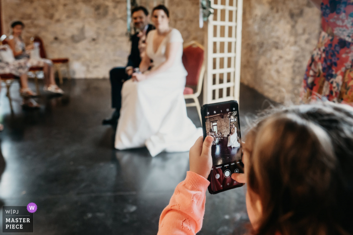 wedding photograph from the Ceremony venue in Toulouse, France of the Grooms little niece taking iPhone pictures during the ceremony