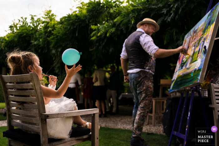 Utrecht wedding photographer at Kasteel Maurick in Vught shooting images of the Flowergirl playing while watching the live painter