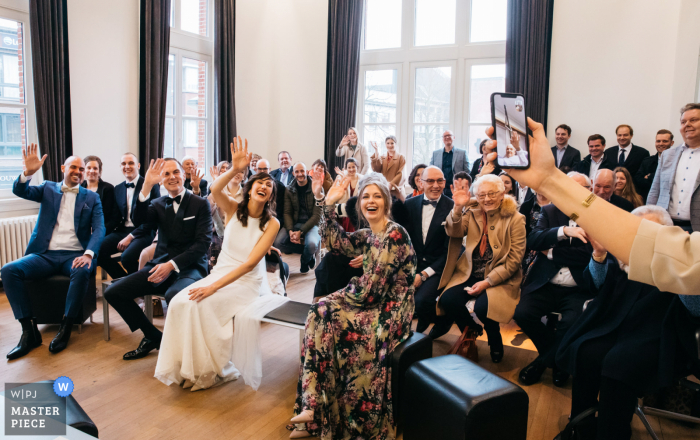 Belgium Wedding Photography | The bride's palliative dad waves and watches his daughter getting married in the town hall through an ipad