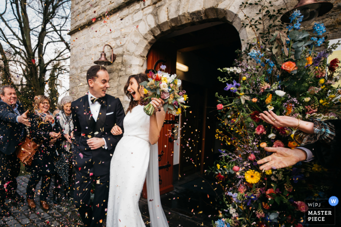 wedding reportage photography from a Flanders Church of the bride and groom leaving the ceremony