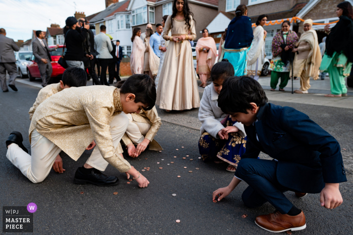 wedding photography from  London, UK of Kids picking up change after Asian wedding ceremony