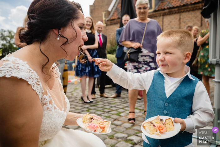 Netherlands wedding photo of a boy feeding the bride during the toast part of the reception