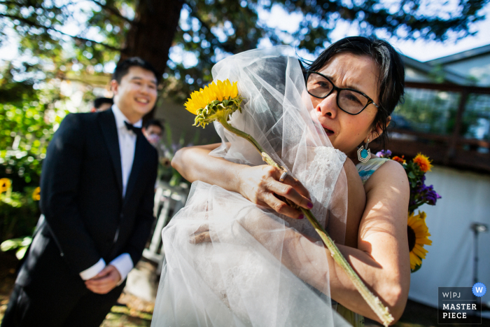 It's hard for the Mom to let go of her 'little' girl in this outdoor wedding image from San Francisco California at a Home backyard event