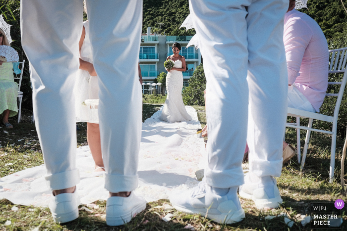 Bride walking down the aisle at a privately set up wedding in front of her house. Shot through the legs of the groom and the couple at Sai Kung, Hong Kong (Outside the Bride & Groom house where they set up for a private wedding due to COVID-19 restriction