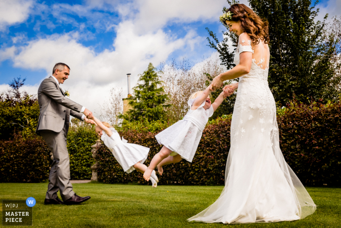 Wedding photo of Bride and Groom being Mama and Dada and spinning their two little girls during the reception at Glenview Gardens, Cork, Ireland