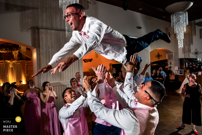 Wedding venue image of the Groom being thrown into the air by groomsmen at Bella Sera Event Center of Brighton, CO