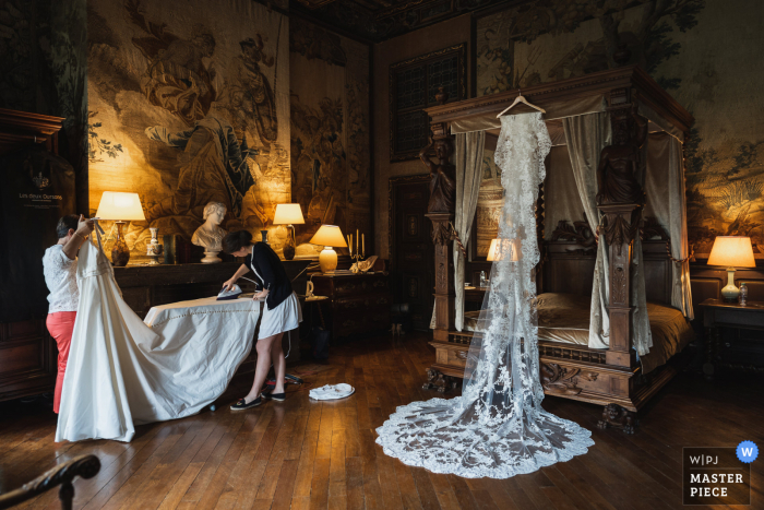 Image of The bride ironing her dress before her wedding at Château de Brissac, France