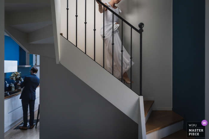 Dinard, France bride going down the stairs before her town hall civil wedding ceremony