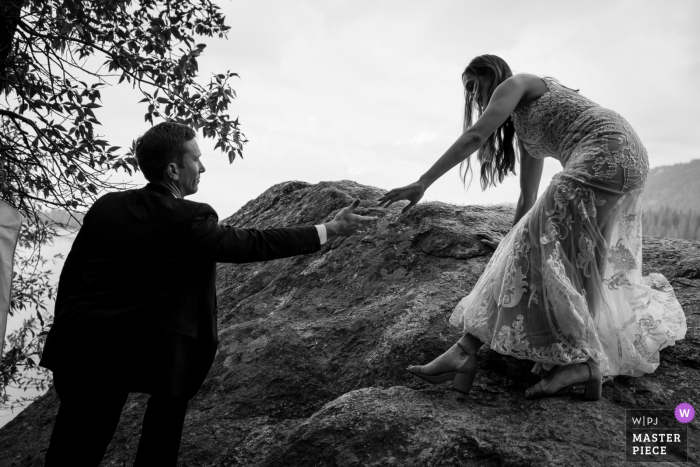 Image of the The groom helping his bride down from the location they chose to read their vows and self marry during their elopement in Wyoming