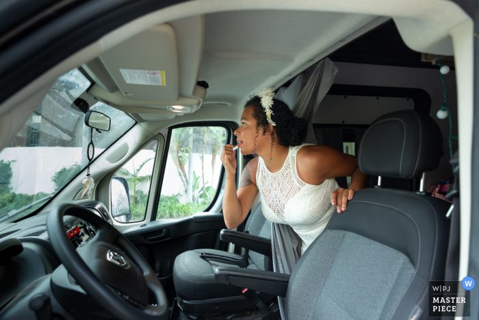 The bride is putting on lipstick in the rented van at the Santa Barbara Courthouse, Ca