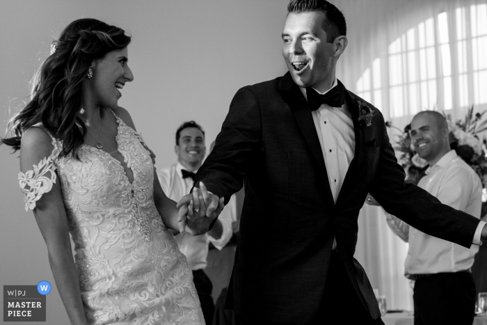 A Bride and Groom walk into wedding reception at the Belle Mer event venue