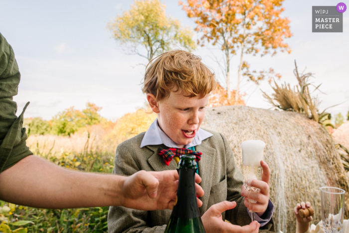 Boy is excited and curious about the (non-alcoholic) bubbly at a Tamworth, Ontario wedding